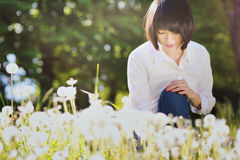 Beautiful asian girl in dandelion flower field royalty free stock images
