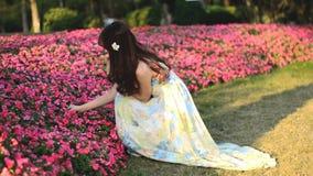 Beautiful Asian girl dressed in long dress playing in the garden. Beautiful Asian girl dressed in long dress, playing in the garden, gently picking flowers stock video footage