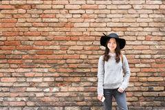 Beautiful asian girl in fashionable dress, standing in front of red brick wall background with copy space Stock Image