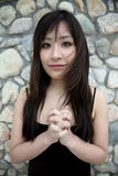 Beautiful Asian girl with hands clasped Stock Photography