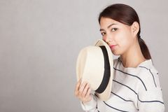 Beautiful Asian girl hold  a  hat close her mouth Stock Photo
