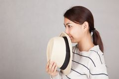 Beautiful Asian girl hold  a  hat close her mouth Royalty Free Stock Photo