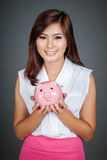 Beautiful Asian girl hold a pink pig money box Stock Photo