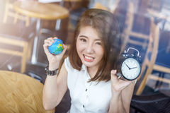Beautiful asian girl holding a globe and black alarm clock royalty free stock photography