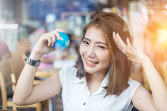 Beautiful asian girl holding a globe in her hand in cofffee sho stock photo