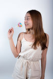 Beautiful asian girl  holding a lollipop with joy. Royalty Free Stock Photography