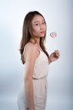 Beautiful asian girl  holding a lollipop with joy. Stock Photo