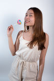 Beautiful asian girl  holding a lollipop with joy. Stock Photography