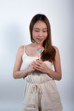 Beautiful asian girl  holding a lollipop with joy. Royalty Free Stock Image
