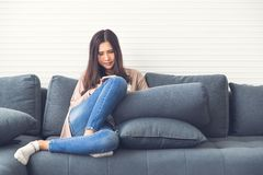 Beautiful Asian girl in jeans is smiling and sitting on couch o royalty free stock photo