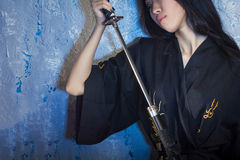 Beautiful Asian girl in kimono with a katana Royalty Free Stock Photography