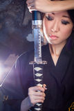 Beautiful Asian girl in kimono with a katana Royalty Free Stock Images