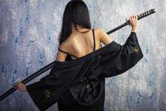 Beautiful Asian girl in kimono with a katana royalty free stock image