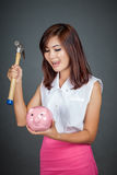 Beautiful Asian girl lick her lips about to hit money box with h Royalty Free Stock Photography