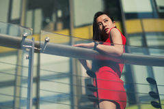 Beautiful Asian girl model in red dress posing at the modern music note style city background. Stock Photography