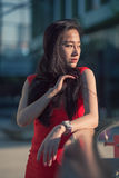 Beautiful Asian girl model in red dress posing at the modern style city park background. Stock Images