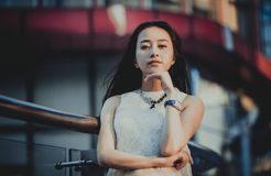 Beautiful Asian girl model in white dress posing at the modern glass style office city background. Royalty Free Stock Photos