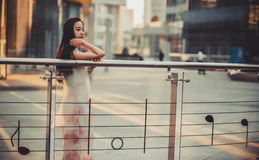 Beautiful Asian girl model in white dress posing at the modern music note style city background. Stock Photos