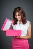 Beautiful Asian girl open a pink gift box and smile Stock Image