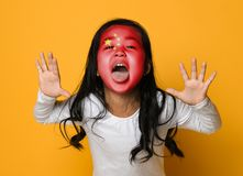 Beautiful asian girl with a painted Chinese flag shows tongue and has fun royalty free stock photo
