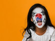 Beautiful asian girl with a painted korean flag shows tongue and has fun stock images