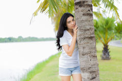 Beautiful Asian girl in the park. And hugging the coconut tree Stock Photos