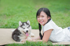 Beautiful asian girl playing with siberian husky puppy Royalty Free Stock Image