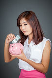 Beautiful Asian girl put a bill to pink pig money box Royalty Free Stock Photo