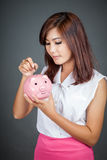 Beautiful Asian girl put a coin to pink pig money box Stock Image