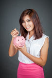 Beautiful Asian girl put a coin to pink pig money box Stock Photos