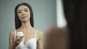 Beautiful Asian girl putting cream on face, standing in front of mirror, beauty. Stock footage stock video