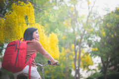 Beautiful Asian girl with red backpack riding bicycle in the park Royalty Free Stock Photos