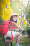 Beautiful Asian girl with red backpack riding bicycle in the park Stock Image