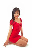 Beautiful asian girl in red dress. Sitting on white Stock Images