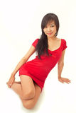 Beautiful asian girl in red dress. Sitting on white Stock Photo