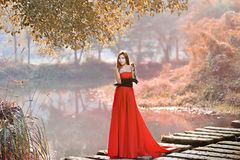 Beautiful Asian girl in red dress frolicking in the countryside. Autumn forest, stream, close to nature, lovely smile royalty free stock photography