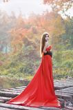 Beautiful Asian girl in red dress frolicking in the countryside. Autumn forest, stream, close to nature, lovely smile stock image