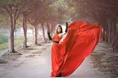 Beautiful Asian girl in red dress frolicking in the countryside. Autumn forest, stream, close to nature, lovely smile stock photo