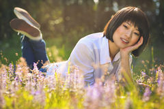 Beautiful asian girl relaxing among flowers Stock Photos