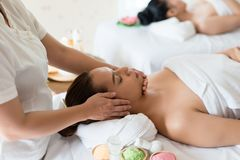 Beautiful Asian girl relaxing receiving facial massage in a spa stock photography