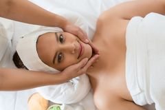 Beautiful Asian girl relaxing receiving facial massage in a spa. Salon stock photography
