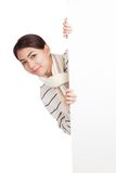 Beautiful Asian girl with scarf peeking from behind blank sign Stock Image