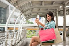 Asian shopping girl selfie by smartphone. Beautiful Asian girl selfie or take photo by smartphone in Bangkok modern city after shopping with many merchant bags Royalty Free Stock Images