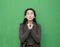 Beautiful Asian girl sends an air kiss. Royalty Free Stock Photos