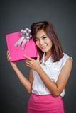 Beautiful Asian girl show a gift box next to her face Royalty Free Stock Image