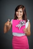 Beautiful Asian girl show a gift box and thumbs up Royalty Free Stock Photography