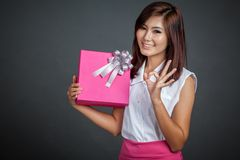Beautiful Asian girl show OK with a gift box Royalty Free Stock Images
