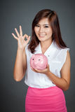 Beautiful Asian girl show OK sign with a pink pig money box Stock Images