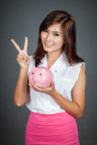 Beautiful Asian girl show victory sign with a pink pig money box Stock Images