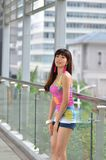 Beautiful Asian girl showing youthful vigor on the pedestrian bridge. Sweet smile, hot body, sexy, youthful, unrestrained Stock Photo